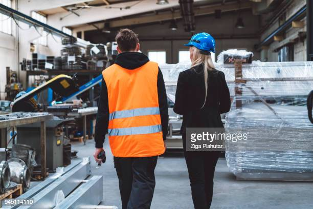 female supervisor and worker walking trough the warehouse - metallic suit stock photos and pictures