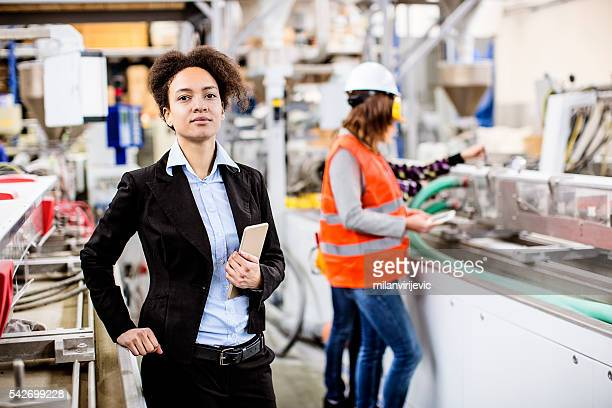 Female supervisor in the factory holding the tablet
