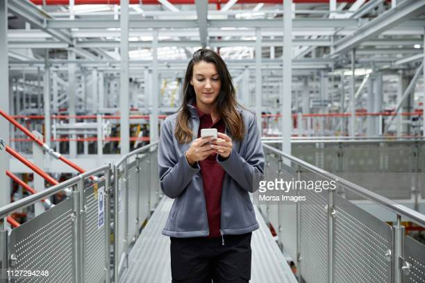female supervisor using mobile phone at car plant - manufacturing stock pictures, royalty-free photos & images