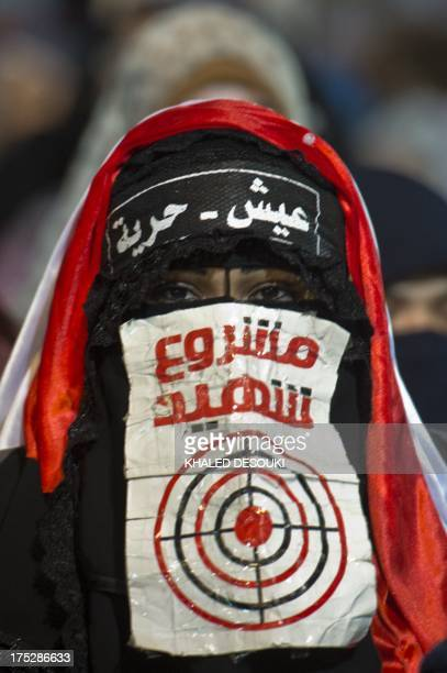 A female supporter of Egypt's deposed president Mohamed Morsi puts an Arabic slogan 'Martyr project ' during an open sit in outside Rabaa alAdawiya...