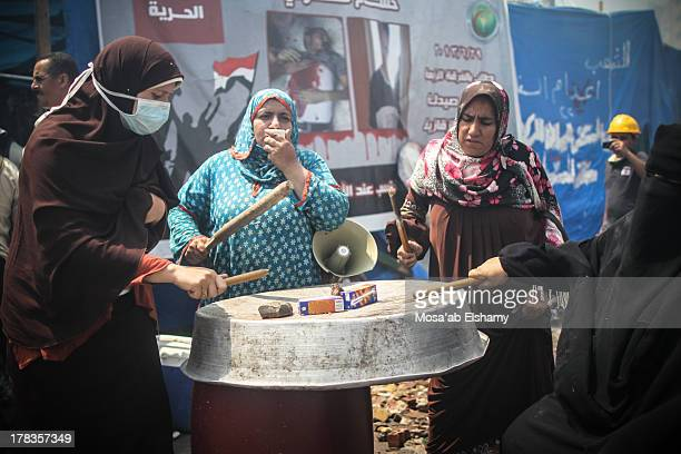 Female supporter of ousted president Mohamed Morsi are seen banging on cooking pots and sitting amid the rubble during the clearing of one of the two...