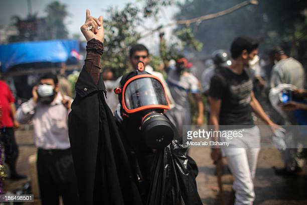 Female supporter of ousted president Mohamed Morsi gestures during the violent dispersal of Rabaa Adaweya camp by security forces on August 14th,...