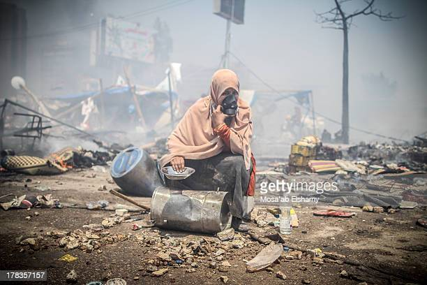 Female supporter of ousted president Mohamed Morsi is seen holding cooking pots and sitting amid the rubble during the clearing of one of the two...