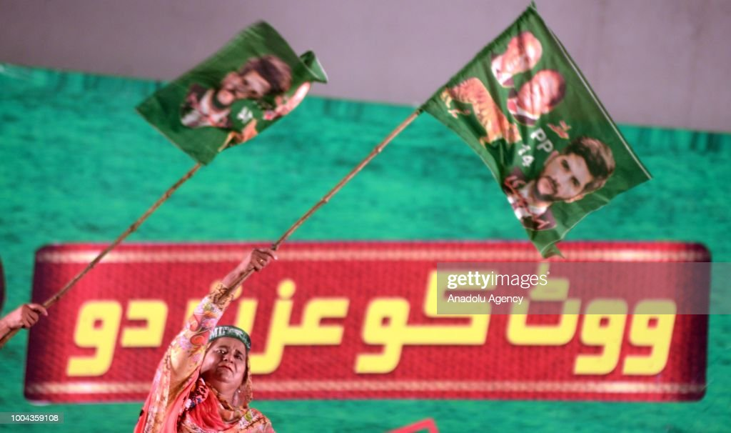A female supporter of Pakistan Muslim LeagueNawaz holds a party flag bearing an image of ousted Prime Minister Nawaz and his brother Shahbaz Sharif...