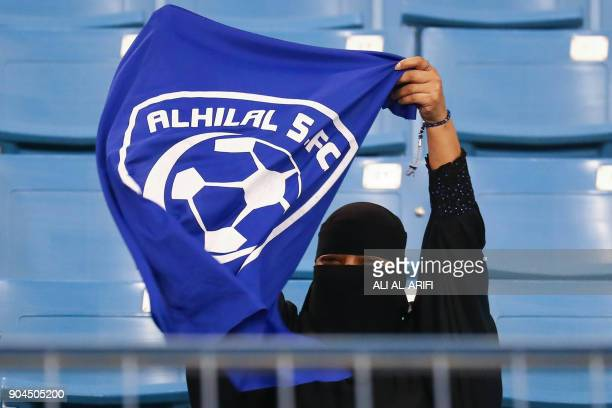 A female supporter of Saudi's AlHilal attends her team's football match against AlIttihad in the Saudi Pro League at the King Fahd International...