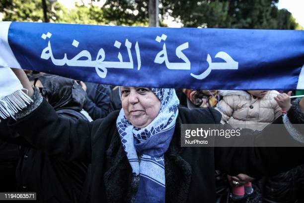 A female supporter wearing a veil holds up a scarf of the moderate Islamist Ennahda party as attends the celebrations of the 9th anniversary of the...