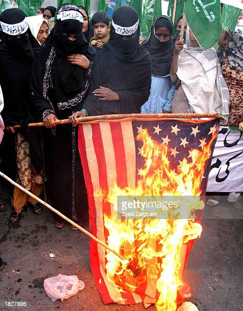 Female supporters of an Islamic party burn an American flag during a protest rally against a possible US attack on Iraq March 4 2003 in Karachi...