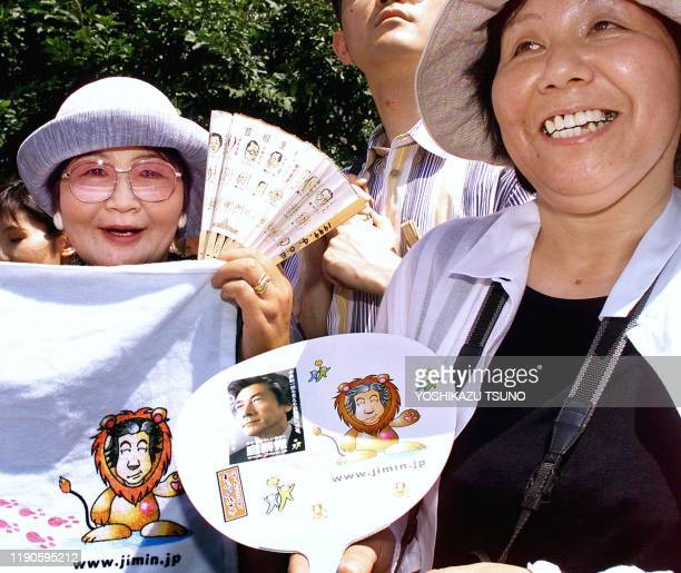 Female supporters of Japanese Prime Minister Junichiro Kizumi display a towel and a paper fan with Koizumi's portrait and illustration as a...