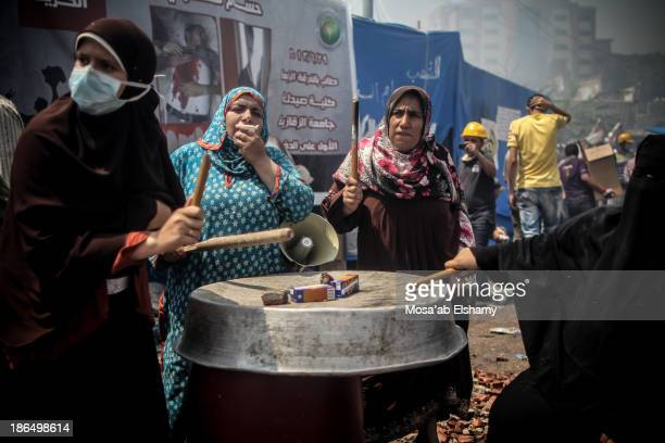 Female supporters of ousted president Mohamed Morsi bang on metal during the violent dispersal of Rabaa Adaweya camp by security forces on August 14,...
