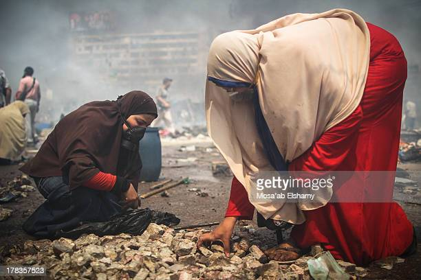 CONTENT] Female supporters of the Muslim Brotherhood and Egypt's ousted president Mohamed Morsi gather stones during clashes with police in Cairo on...