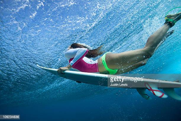 Female surf duck diving under a large wave.