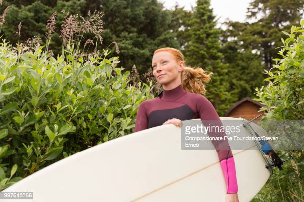 Female surfer carrying board on path
