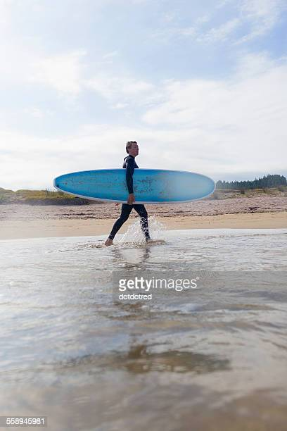 Female surfer carrying surfboard in sea, Bay of Islands, New Zealand