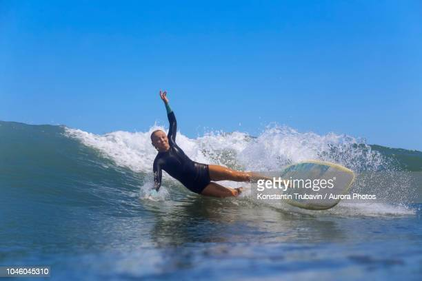 female surfer falling off surfboard while riding wave, male, maldives - falling stock pictures, royalty-free photos & images