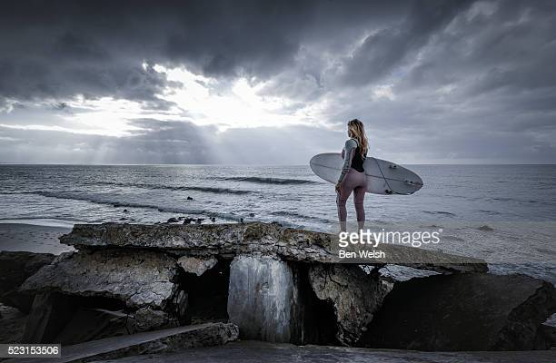 Female surfer looking at the Atlantic Ocean.