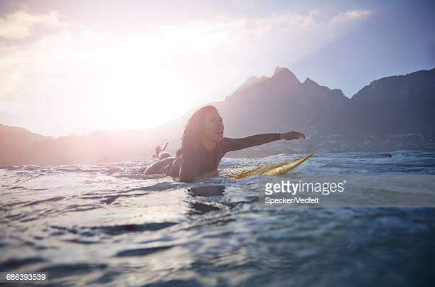Female surfer paddling at sunrise