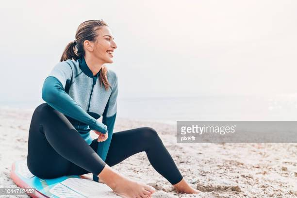 female surfer resting on the beach - wetsuit stock pictures, royalty-free photos & images