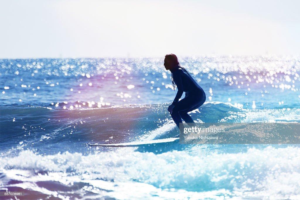 Female surfer riding the wave : ストックフォト