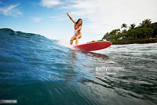 Female surfer riding wave view from water