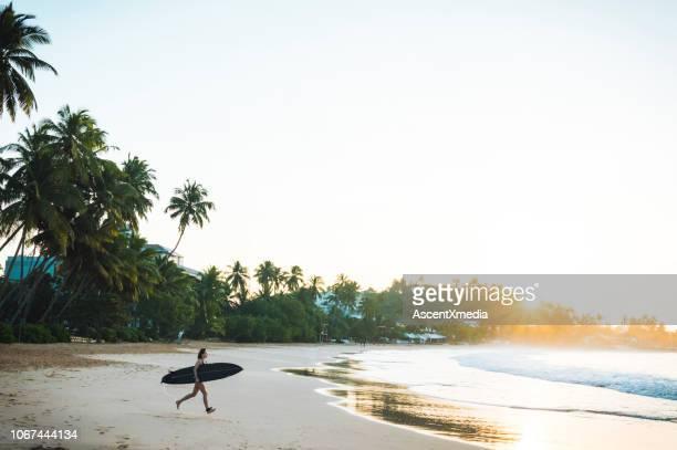 surferin läuft in richtung wasser - sri lanka stock-fotos und bilder
