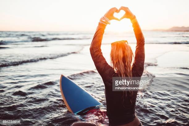 vrouwelijke surfer weergegeven: liefde - branding stockfoto's en -beelden