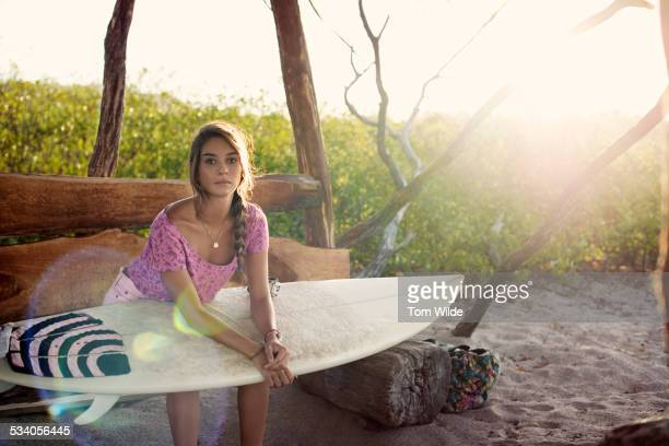Female surfer sitting on a bench holding her board