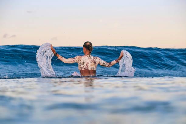 Female surfer splashing water during sunset
