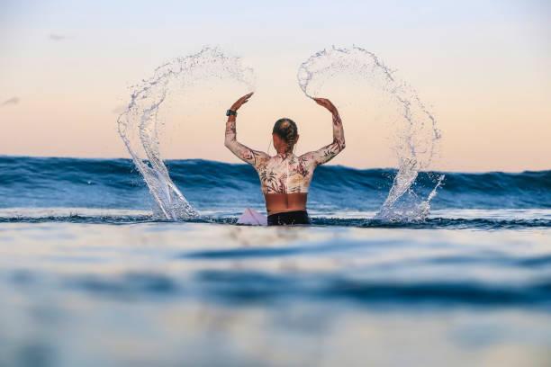 Female surfer splashing water in sea during sunset