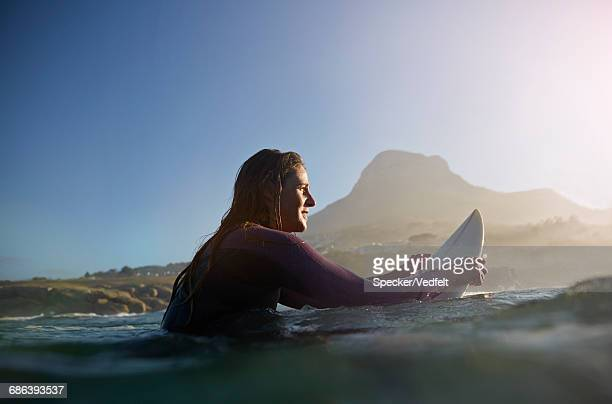 female surfer waiting for the perfect wave - wading stock pictures, royalty-free photos & images