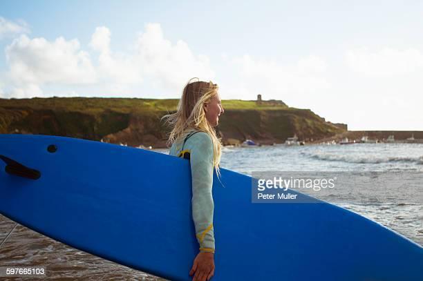 Female surfer walking toward sea, carrying surfboard