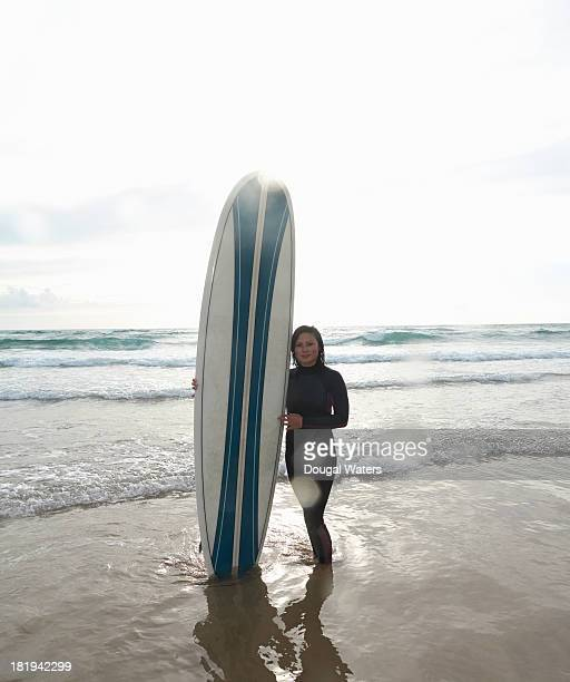 female surfer with board at beach. - dougal waters stock pictures, royalty-free photos & images