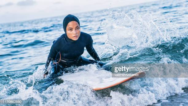 female surfer with hijab in sea - extreme sports stock pictures, royalty-free photos & images