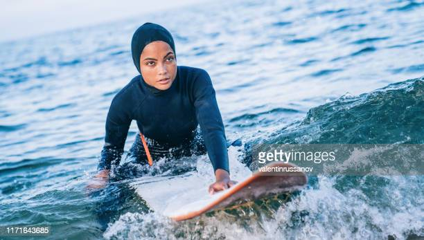 Female surfer with hijab in sea