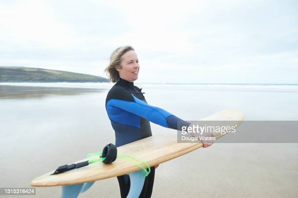 female surfer with surfboard at beach. - dougal waters stock pictures, royalty-free photos & images