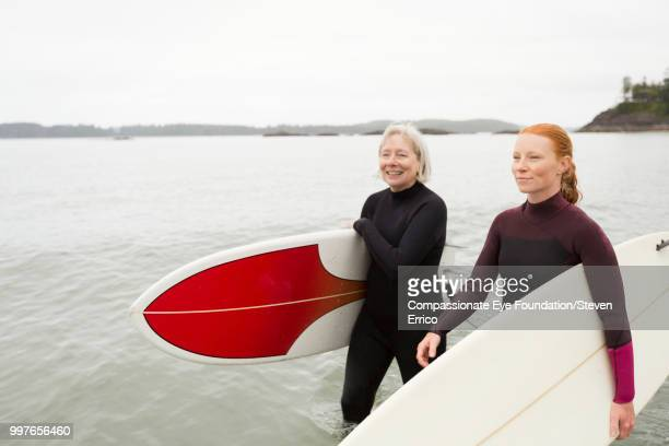 female surfers carrying boards walking along beach - older redhead stock pictures, royalty-free photos & images