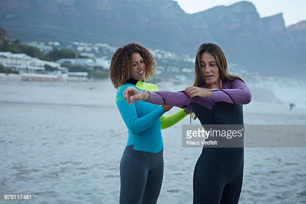 Female surfers getting in wetsuits at the beach