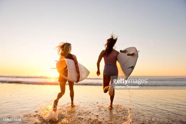 female surfers running on the beach at sunset - california stock pictures, royalty-free photos & images