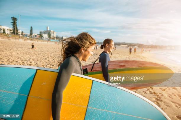 female surfers rushing to catch a waves - wetsuit stock pictures, royalty-free photos & images