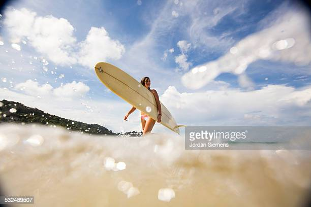 A female surfing in tropical water.