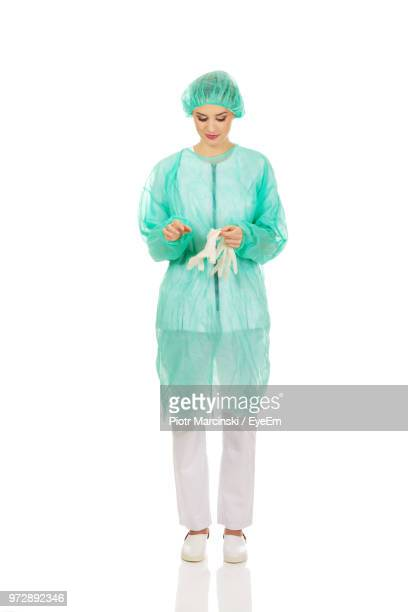 female surgeon holding surgical gloves against white background - operating gown stock pictures, royalty-free photos & images
