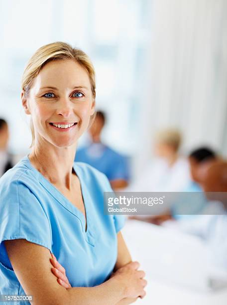 Female surgeon smiling with colleagues at the back