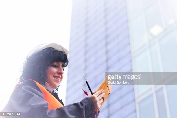 female surveyor looking at distance meter outside office building - sigrid gombert stock-fotos und bilder