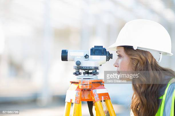 female surveyor looking through level on construction site - surveyor stock photos and pictures