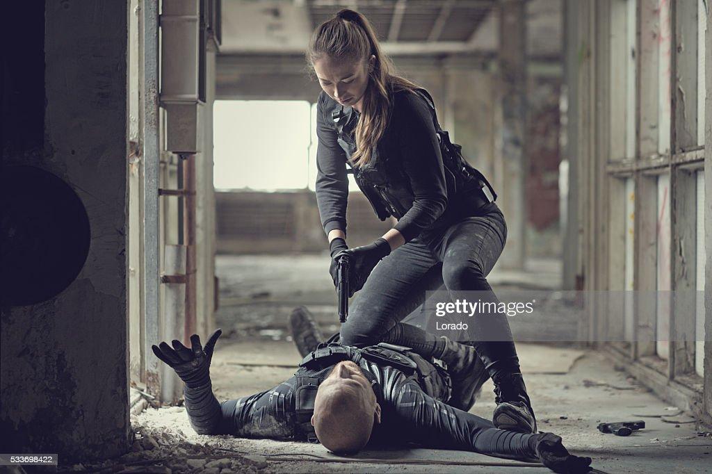 Feminino swat funcionário incríveis em gunpoint masculino insurgent : Foto de stock