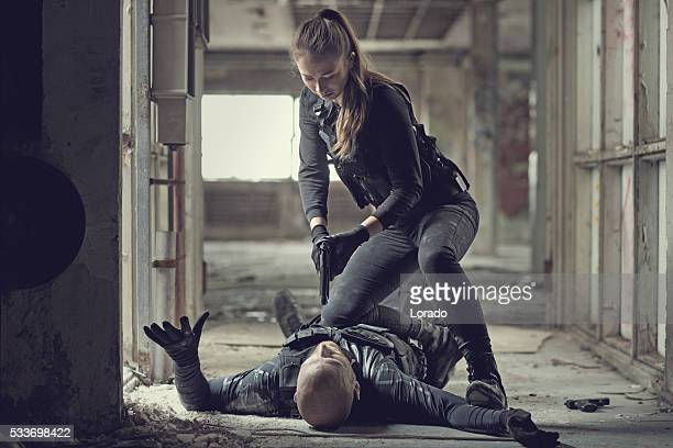 female swat team member arresting male insurgent at gunpoint - women dominating men stock photos and pictures