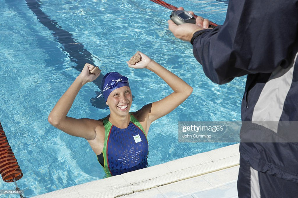 Female Swimmer at the Edge of a Swimming Pool Being Timed by Her Coach : Stock Photo
