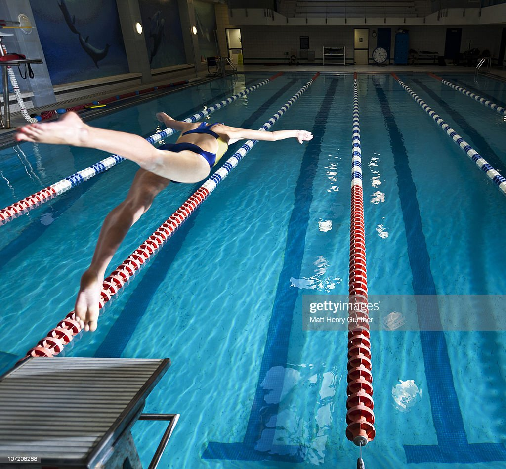 Female Swimmer Diving Into Pool Stock Photo