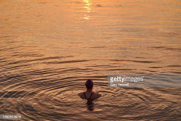 female swimmer in the sea at sunset - freedom stock pictures, royalty-free photos & images
