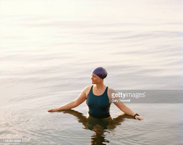 female swimmer in the sea at sunset - swimming stock pictures, royalty-free photos & images