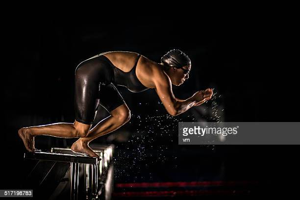 Female Swimmer Jumping Off The Starting Block